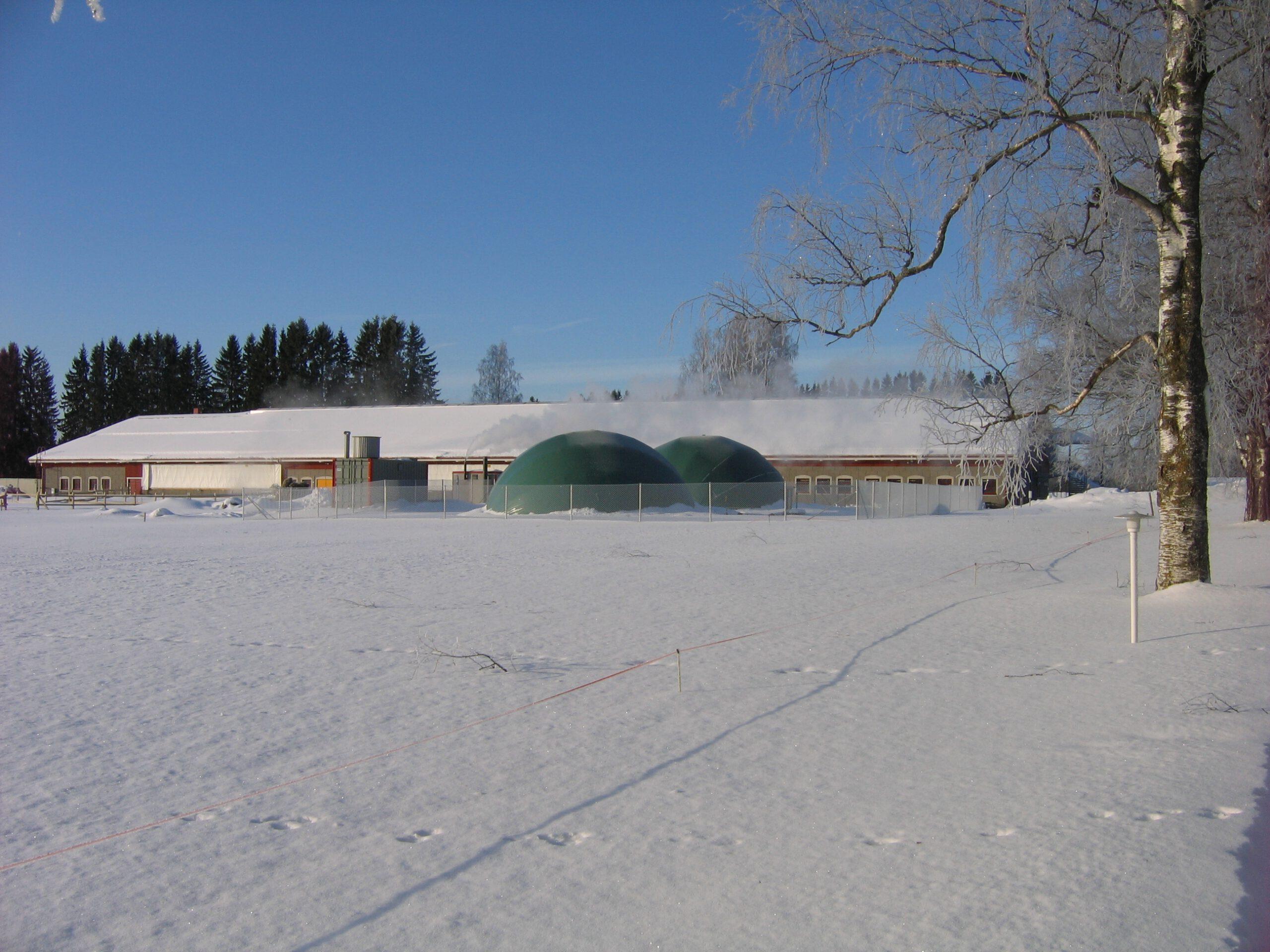 Biokaasutuotantolaitos talvisessa maisemassa maaeudulla
